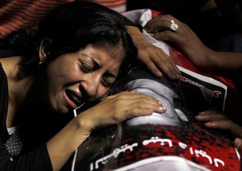 WOMAN MOURNS ON COFFIN OF VICTIM KILLED DURING PROTEST IN CAIRO