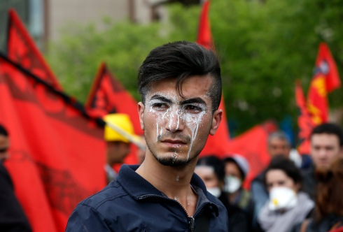 Protester, with cream applied to his face to protect against tear gas, reacts during a May Day demonstration in Istanbul